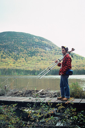 A vertical stock photograph of a young man carrying his camera and tripod over his shoulder at Lonesome Lake white mountains,new hampshire.