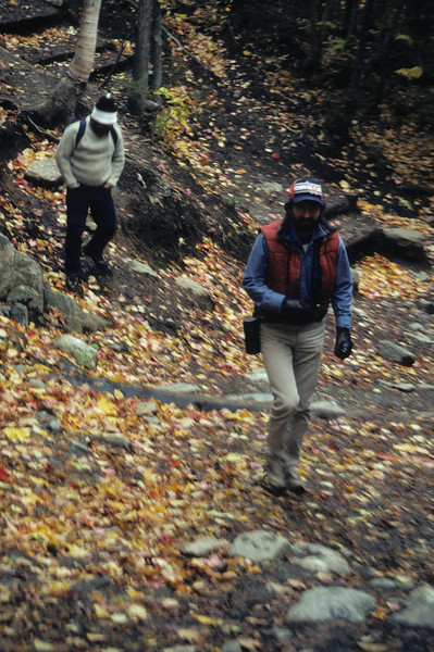 A vertical stock photograph of two young men hiking on a trail in autumn.