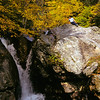 A vertical stock photograph of a young Filipino american boy setting on rocks overlooking a waterfall. White Mountains,New Hampshire