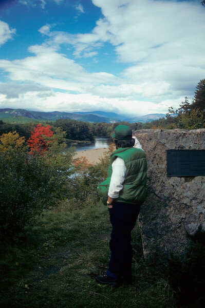 A vertical stock photograph of a young man gazing out over Saco Valley White Mountains New Hampshire.