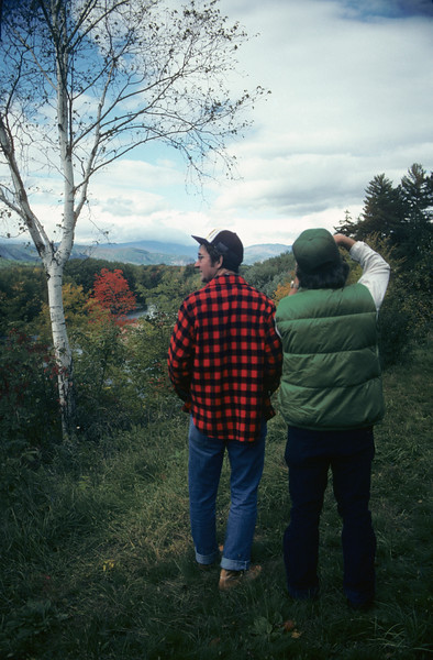 A vertical stock photograph of two young men photographing the autumn beauty overlooking the Saco River Valley in White Mountains of New Hampshire.