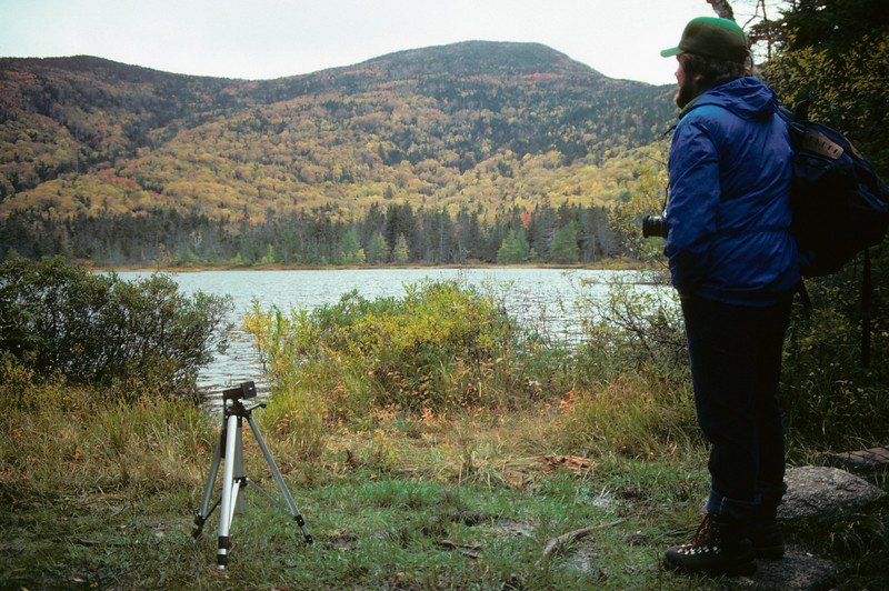 A horizontal stock photograph of a young man enjoying the mountain scene at Lonesome, Lake White Mountains, New Hampshire, before he takes a photograph.His tripod set in the foreground.