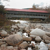 A horizontal view of the Albany covered bridge spanning the Swift river in White Mountains New Hampshire. Large boulders in the foreground.