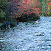 A vertical stock photograph of two young men capturing autumn color along a river in New hampshire's white mountains.
