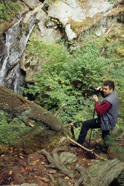 A vertical stock photograph of a nature photographer setting up his shot of a small waterfall.
