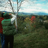 A vertical stock photograph of two young men photographing autumn beauty of the Saco River Valley. Located in the White Mountains New Hampshire.