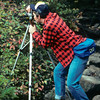 A vertical stock photograph of a young man peering through his tripod mounted camera to photograph fall foliage