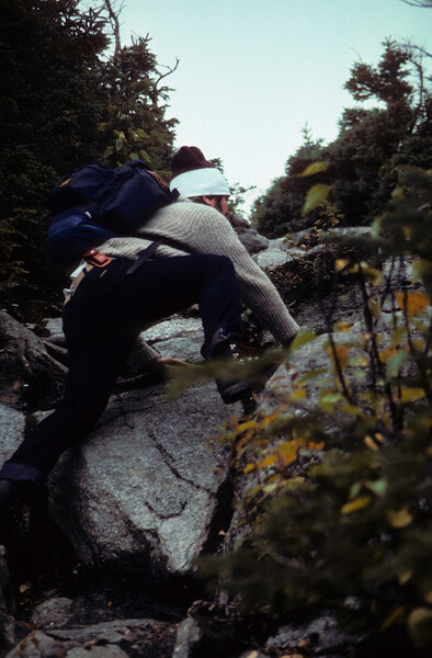 A vertical stock photograph of a young man climbing up a steep trail  carrying  a backpack.