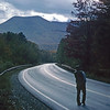 A Vertical Stock Photograph of a man looking down a hard top winding road.The road is strongly backlit by the sun after a storm.