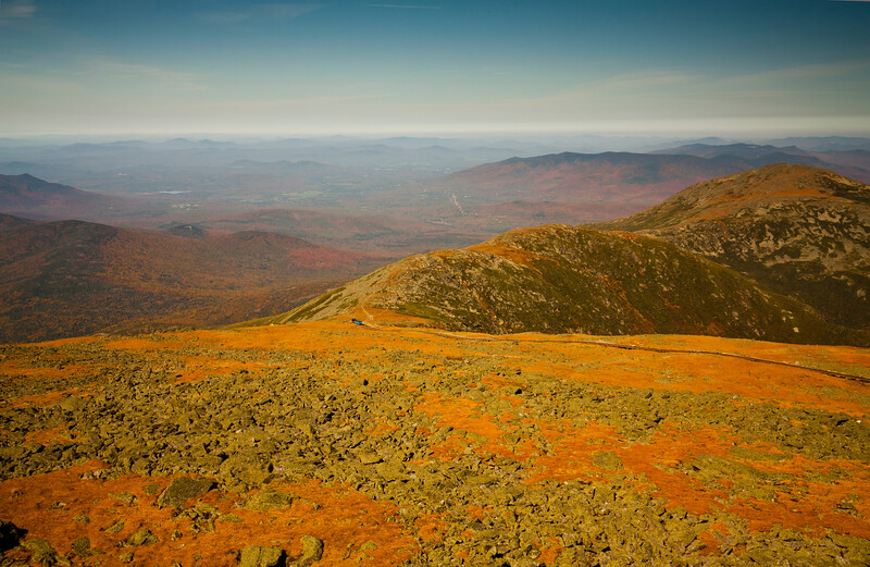 A horizontal stock photograph  of   a fall scenic view from the summit of Mt. washington, showing  cog railway locomotive and great gulf wilderness in the distance.