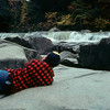 A vertical stock photograph of a young man laying on large rocks to photograph rushing water.New Hampshire White Mountains.
