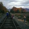 A vertical stock photograph of three young men photographing along the railroad tracks in Pondicherry Wildlife Refuge.White Mountains,New Hampshire.