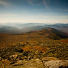 A horizontal stock photograph  of   a fall scenic view from the summit of Mt. washington, showing Lake of the Clouds AMC hut in distance.