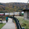 A horizontal stock photograph of a man and a woman viewing a freight train carrying stacked truck boxes at Horseshoe Curve National Historic Landmark. Altoona Pennsylvania.