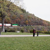 A horizontal stock photograph showing a man photographing a Northfolk Southern freight train passing by. Horseshoe Curve National Landmark, Altoona Pennsylvania.