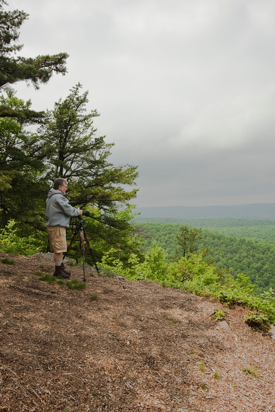 A vertical stock photograph of a man photographing  the view of Penns Valley in Central Pennsylvania