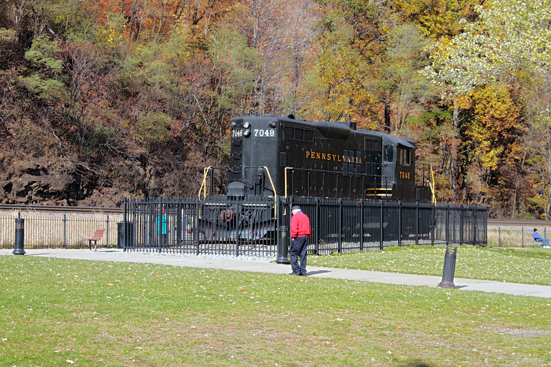A horizontal stock photograph of an elderly man walking by the locomotive display at Horseshoe Curve National Historic Landmark, located in Altoona Pennsylvania.