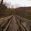 A vertical stock photograph of a wooden bridge built on top of a railroad bridge. Part of the rails to trails project.