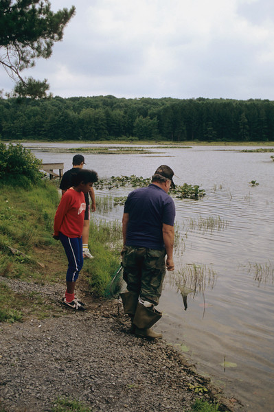 A Vertical Stock Photograph of a man and two preteens looking into a small lake.