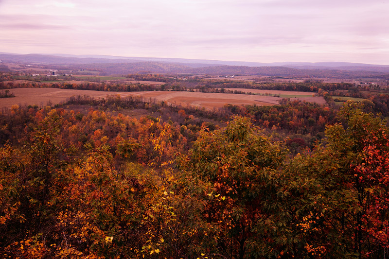 A horizontal stock photo 0f a scenic overlook view showing a farming valley near Tyrone Pennsylvania. Beautiful hardwood Fall foliage in the foreground.