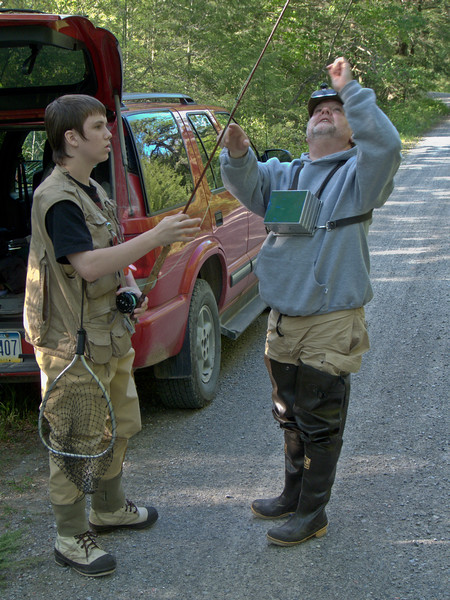 Teenage boy and middle aged man prepare for a fly fishing trip.