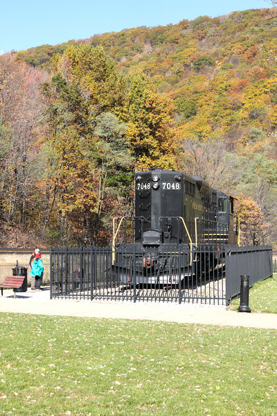 A vertical stock photograph of a man and a woman viewing the locomotive display at Horseshoe Curve National Historic Landmark. Altoona Pennsylvania