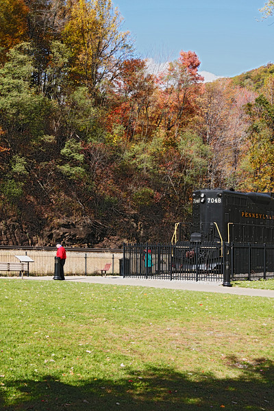A vertical stock photograph of an elderly man walking by the locomotive display at Horseshoe Curve National Historic Landmark