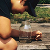 A vertical stock photo of a preteen filipino american boy staring intently into a jar containing a baby catfish.