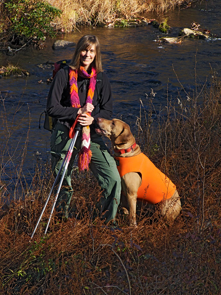 A vertical stock photo of of a young lady and her dog posing near a trout stream,a beautiful autumn day in central Pennsylvania.