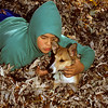 Young boy holding his puppy in fall leaves