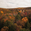 A horizontal Stock Photograph showing a view of the viaduct bridge on I80 in central Pa.Bright fall foliage and the Red Moshannon in foreground.