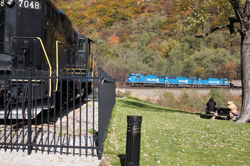 A horizontal stock photograph showing the static display locomotive and a three engine freight train making it's way around horseshoe curve. Altoona Pennsylvania.