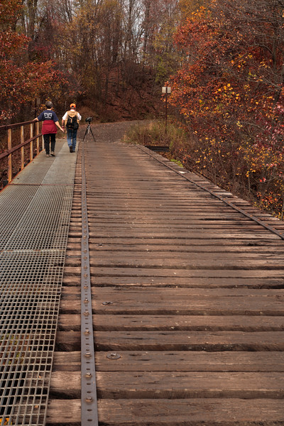 A Vertical Stock Photograph of a man and woman walking on a metal railroad bridge now a rail to trails.