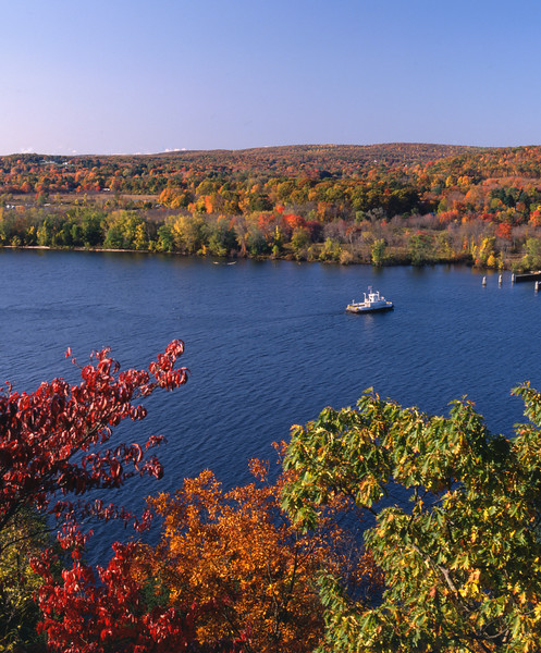 A Vertical Stock Photograph of the Hadlyme Ferry heading into the dock.View from Gillette Castle State Park Connecticut.