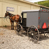 A horizontal stock photo of an amish buggy and horse tied to a rail. Central Pa.