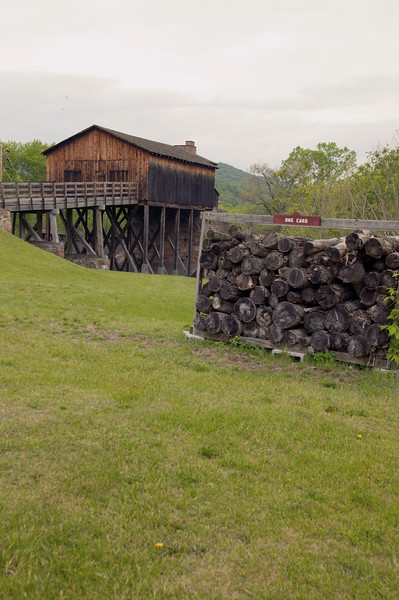 A cord of wood in the foreground with The charging house and forge in the background at Curtin Village iron works in central Pennsylvania.