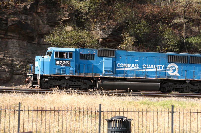 A horizontal stock photograph close view showing  a blue conrail locomotive engineer waving his hand as the train makes it's way around horseshoe curve, Altoona Pennsylvania.