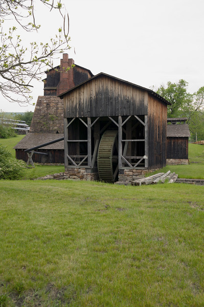 The water wheel that provided power for the Curtin Village iron works in central Pennsylvania with forge in the background.
