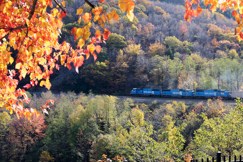 A blue conrail locomotive with  three deisels engines making it's way up the incline at horseshoe curve,Altoona Pennsylvania.