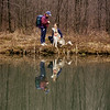 Husband and wife with their Siberian Husky showing reflections in a country pond