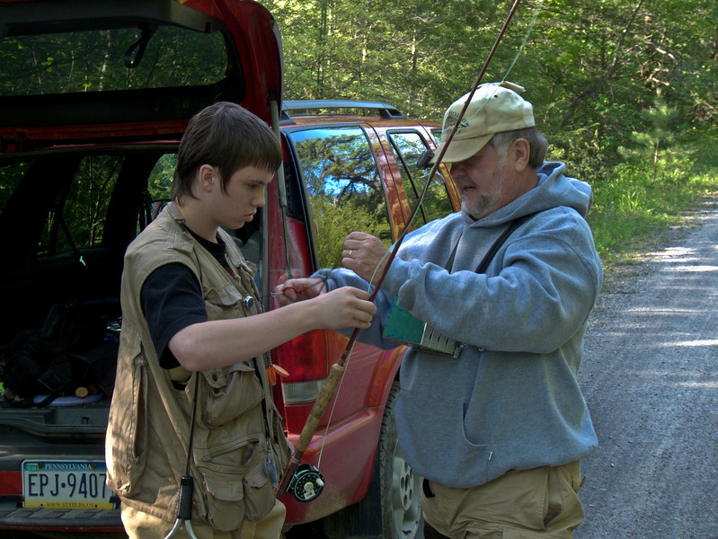A horizontal stock photograph of a Teenage boy and middle aged man getting prepared for a fly fishing trip.