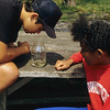 A vertical stock photo of a preteen filipino american boy and a filipino african american girl studying a catfish in a jar.