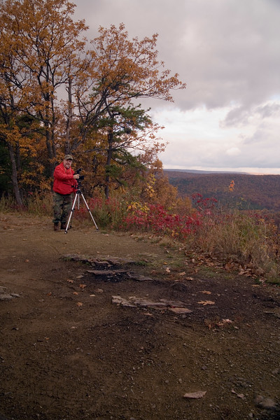 A vertical stock photograph of a man posing beside his tripod mounted camera with beautiful fall scenery in the background.