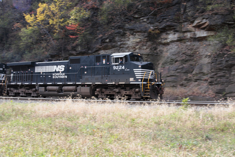 A black Norfolk Southern locomotive the Engineer waving his hand, passes by at Horseshoe National Monument located near Altoona Pennsylvania.