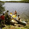 A group of  campers unloading their canoes at Grout Pond Vermont
