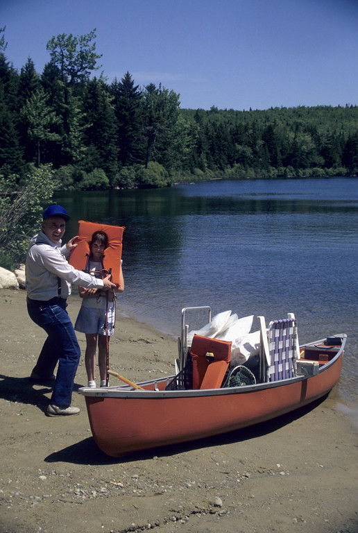 Father and daughter having fun on the beach of Grout Pond,southern vermont. Loaded canoe in foreground.