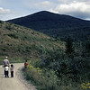 A father taking a walk with young children on a dirt  road  at Somerset reservoir,southern Vermont.