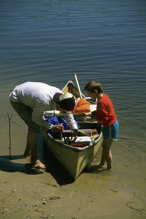 A stock photograph Father and excited son getting ready to launch their canoe.