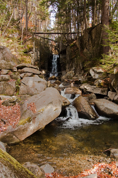 A vertical stock photograph of a waterfall on Flume    in Dixville Notch Vermont. A beautiful autumn day in Vermont.