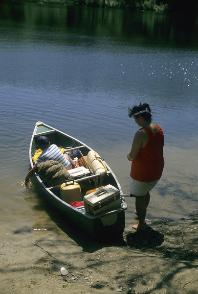 A stock photograph of a teenage girl Teenage sister preparing to launch a canoe with young brother aboard.